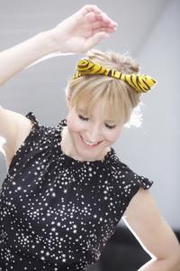 Playful woman in cat costume ears dancing