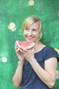 Portrait carefree happy woman eating watermelon