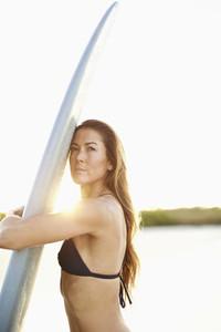 Portrait confident female surfer hugging surfboard