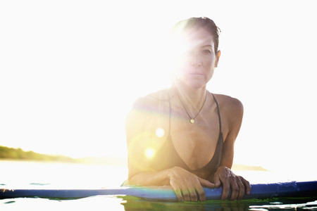 Portrait confident female surfer leaning on surfboard in sunny ocean