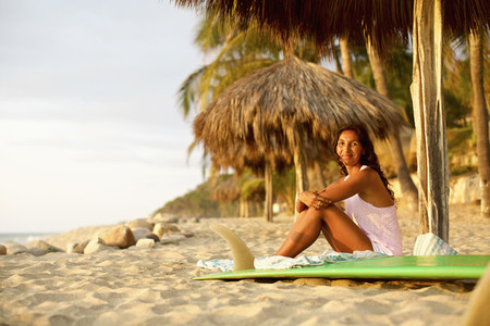 Portrait confident female surfer with surfboard relaxing on sunny beach