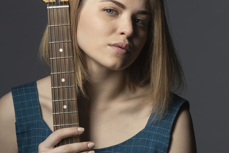 Portrait confident  beautiful young woman with electric guitar