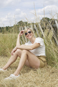 Portrait confident carefree woman sitting in tall grass