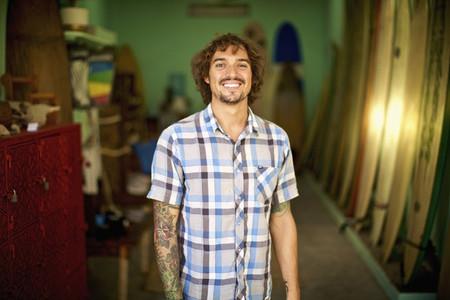 Portrait confident happy male surf shop owner