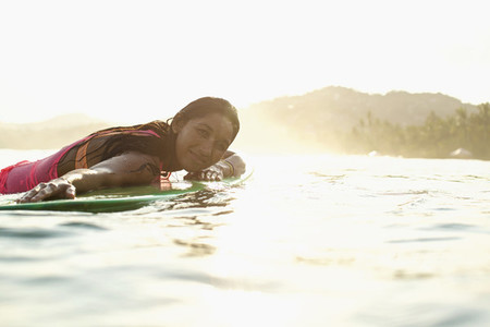 Portrait confident serene female surfer laying on surfboard in sunny ocean