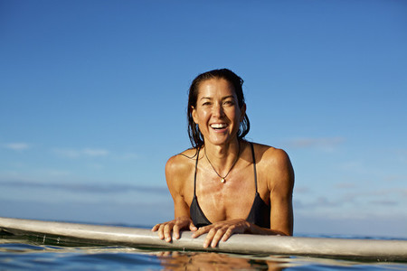 Portrait happy confident female surfer leaning on surfboard in ocean