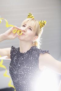 Portrait playful woman wearing cat costume ears