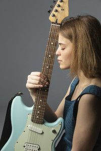 Portrait serene young woman with electric guitar