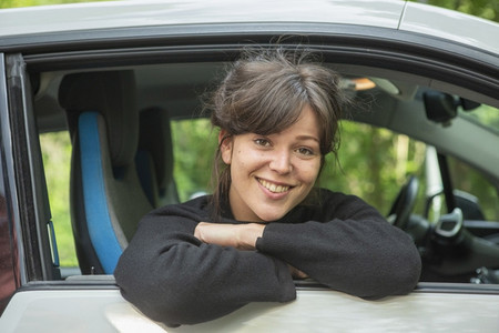 Portrait smiling young woman leaning out car window