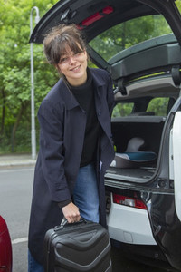Portrait smiling young woman loading suitcase into car