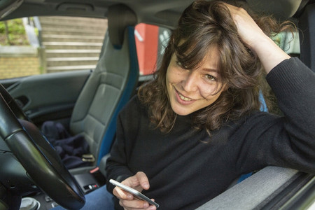 Portrait smiling young woman using smart phone in car