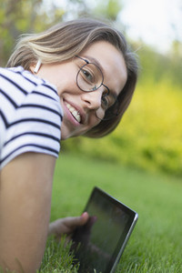 Portrait smiling young woman with digital tablet and headphones in grass