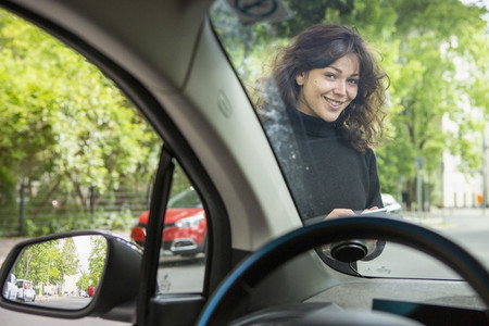 Portrait smiling young woman with smart phone accessing car share