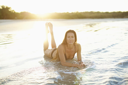 Portrait woman in bikini laying in sunny ocean surf