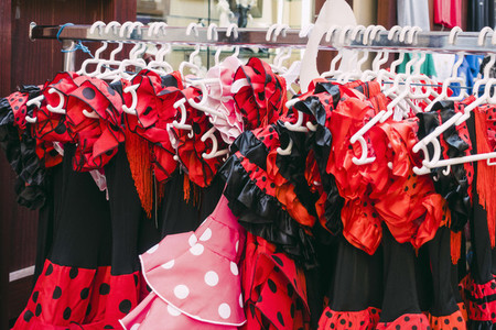 Red and black polka dot costume dresses hanging on clothes rack in shop