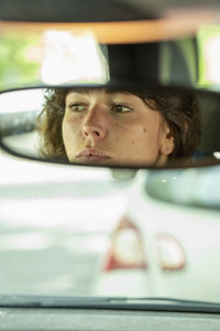 Reflection of woman in rear view mirror driving car