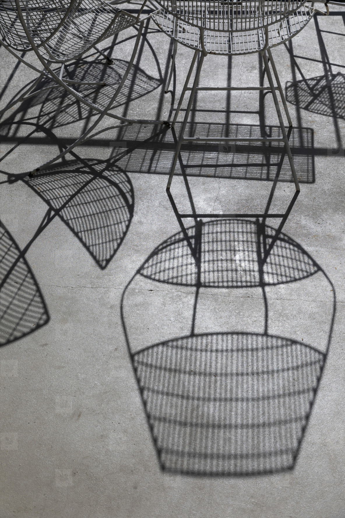 Shadows of iron chairs and table on sunny patio