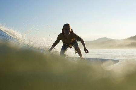 Silhouette boy surfer riding ocean wave