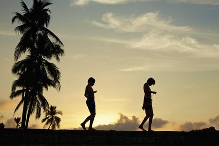 Silhouette boys walking along ledge against tranquil sunset sky