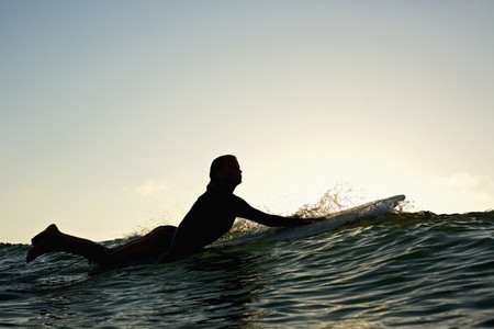 Silhouette female surfer paddling out