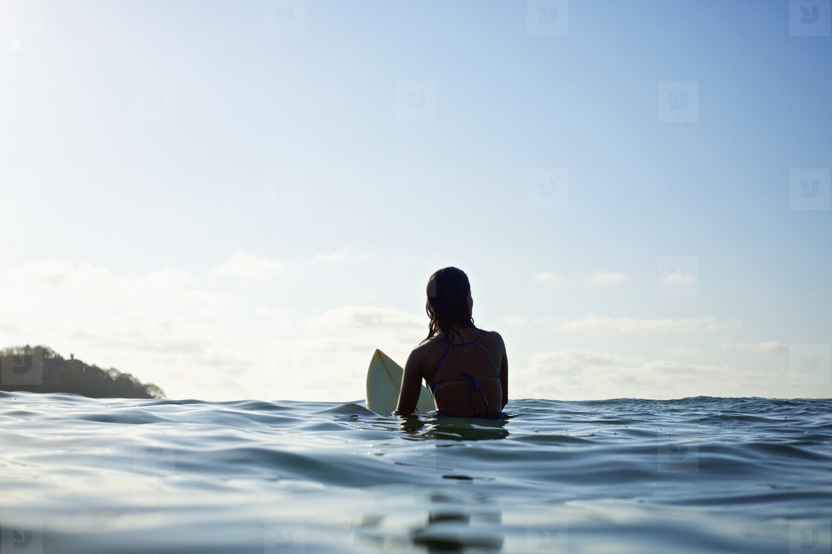 Silhouette female surfer straddling surfboard  waiting in sunny blue ocean