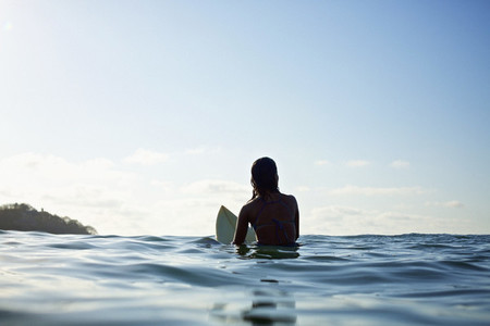 Silhouette female surfer straddling surfboard waiting in sunny blue ocean