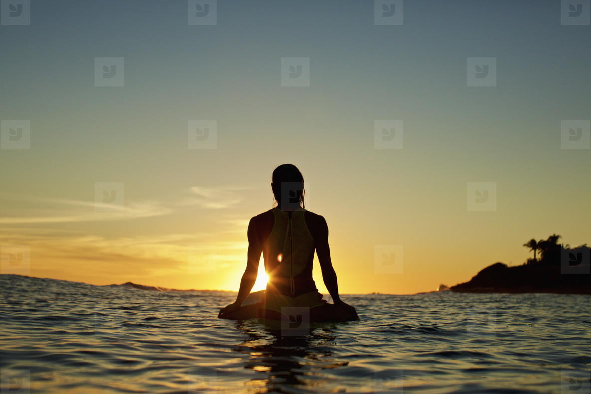 Silhouette female surfer waiting on surfboard on ocean  watching sunset  Sayulita  Nayarit  Mexico