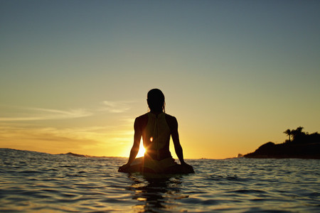 Silhouette female surfer waiting on surfboard on ocean watching sunset Sayulita Nayarit Mexico