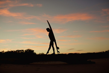 Silhouette female surfer with surfboard on beach at dusk 03