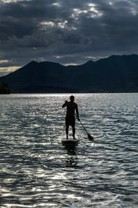 Silhouette man paddleboarding on sunny  idyllic lake  Walchensee  Bavaria  Germany