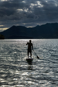 Silhouette man paddleboarding on sunny idyllic lake Walchensee Bavaria Germany