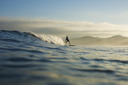 Silhouette paddle boarder riding ocean wave  Sayulita  Nayarit  Mexico