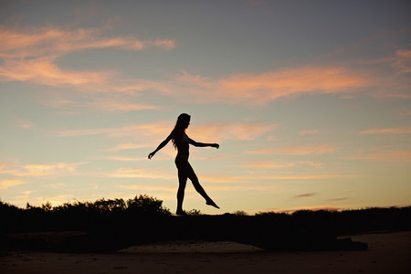 Silhouette woman on beach at dusk 01