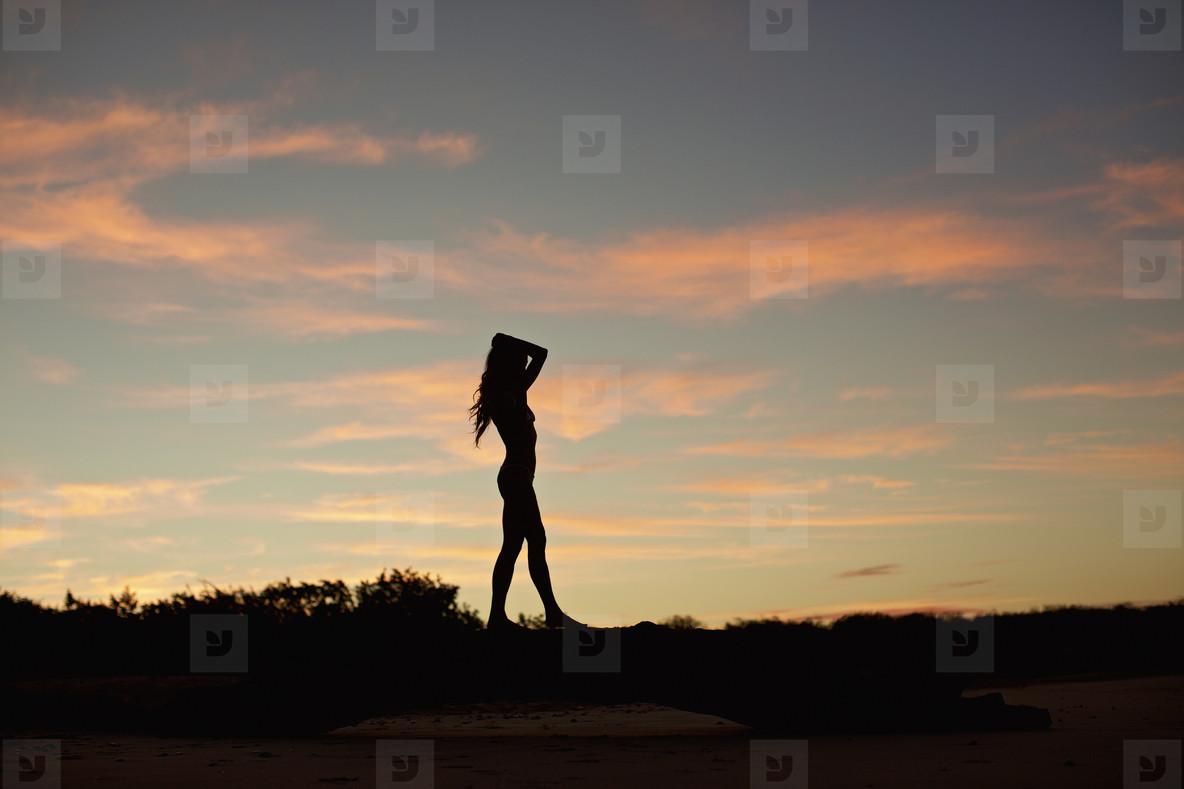 Silhouette woman on beach at dusk 02