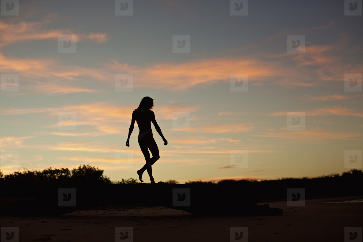 Silhouette woman on beach at dusk 03