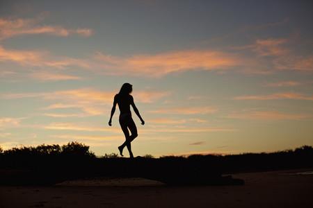 Silhouette woman on beach at dusk 03