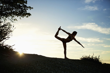 Silhouette woman practicing king dancer yoga pose