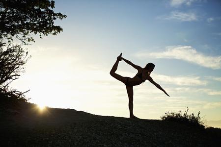 Silhouette woman practicing king dancer yoga pose