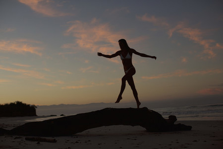 Silhouette woman walking on driftwood on beach at dusk