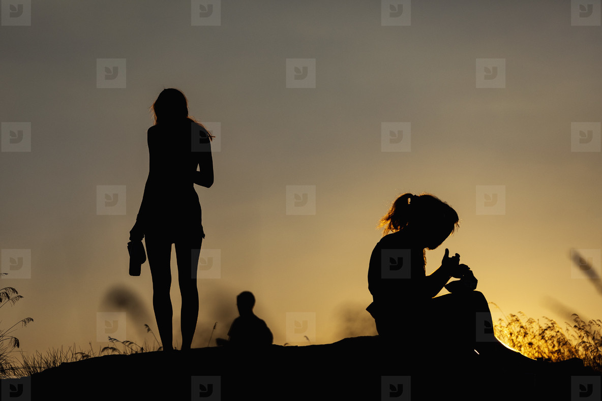 Silhouette women eating and drinking on hill at sunset