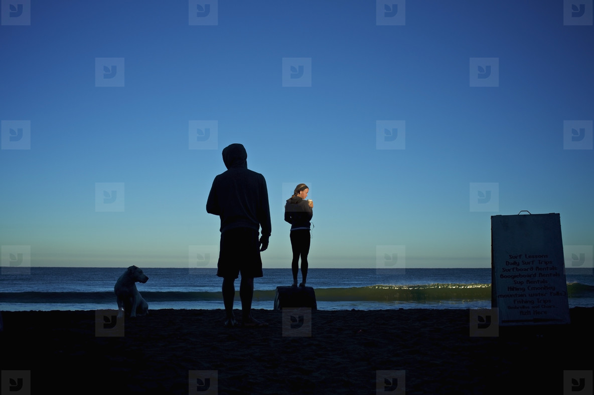 Silhouette young couple with dog on sunrise beach