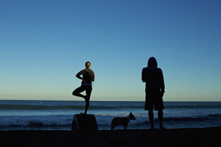 Silhouette young couple with dog practicing yoga on sunrise beach