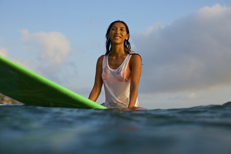Smiling confident female surfer waiting on surfboard in ocean
