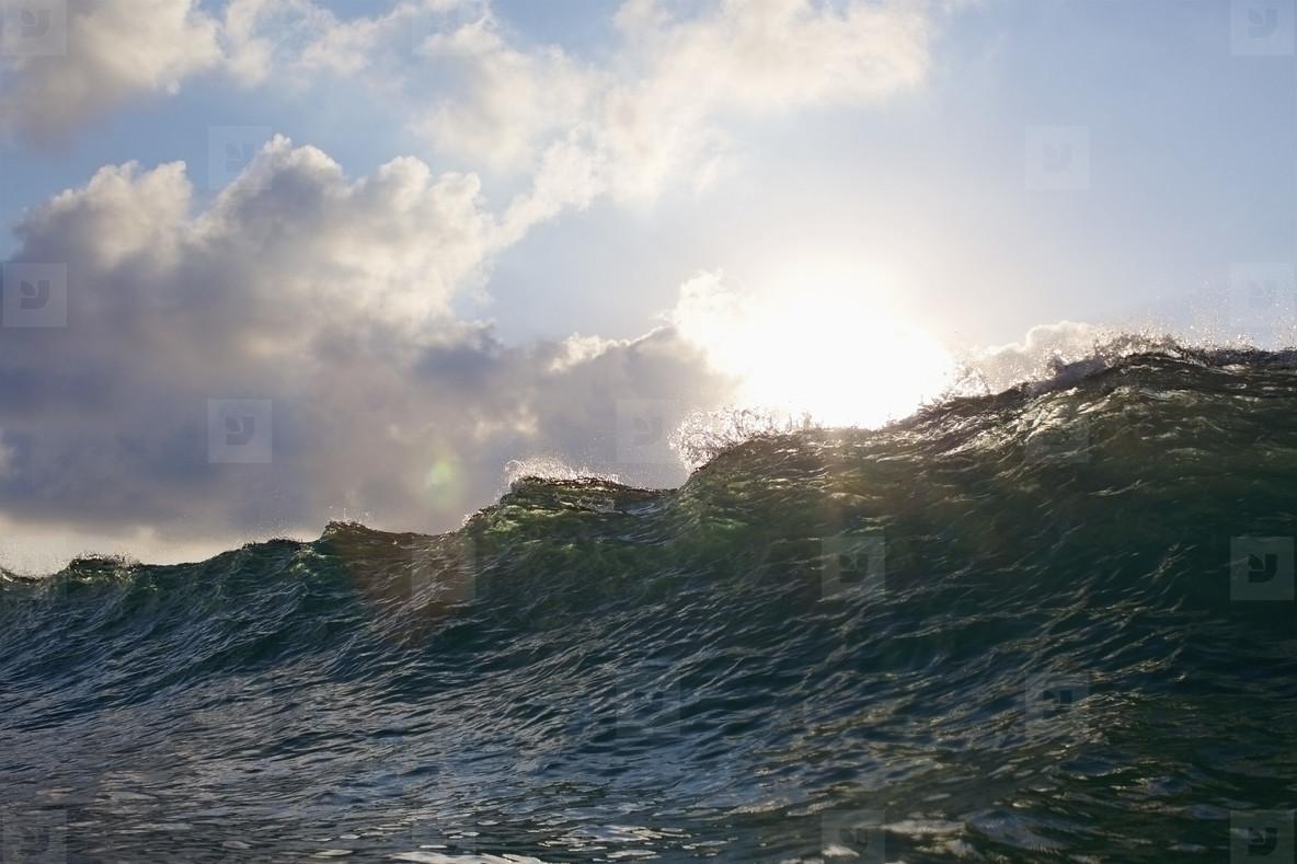 Sun shining over cresting ocean wave