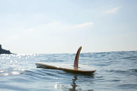 Surfboard floating on sunny blue ocean