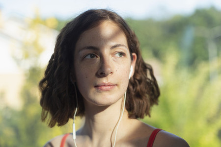 Thoughtful woman listening to music with headphones