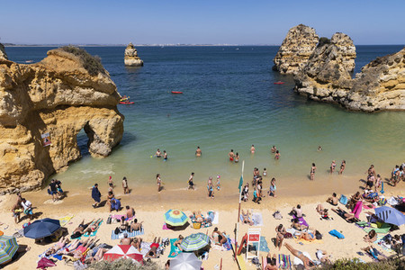 Tourists sunbathing and swimming on sunny  summer beach  Lagos  Algarve  Portugal