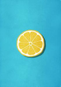 Vibrant yellow lemon slice on blue background