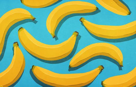 Vibrant  unpeeled yellow bananas on blue background