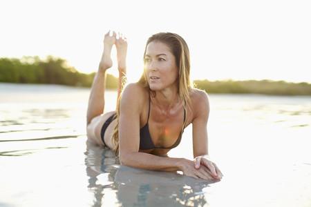 Woman in bikini laying in sunny ocean surf